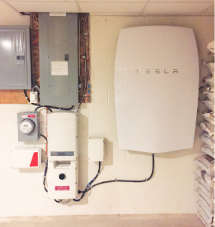 Tesla Powerwall battery (right) with inverter, solar meter and main electrical box in basement of Rife solar home.